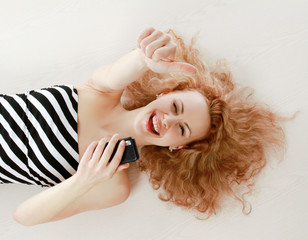 A smiling girl lying on the floor with a mobile