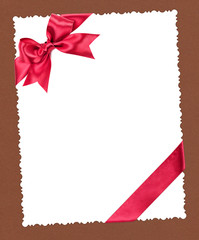 blank paper sheet with red bow on brown