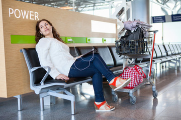 Transit passenger spending time in airport, luggage hand-cart