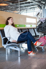 Woman dreaming with pc in airport lounge with luggage cart