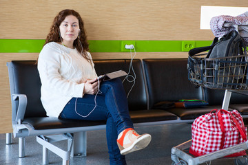 Serene woman charging tablet pc in airport waiting room