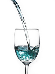 pouring blue water into wine glass on white background