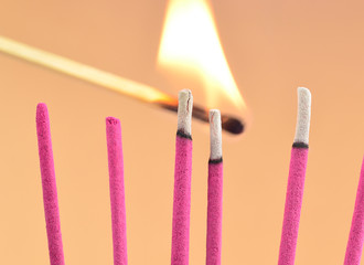 Räucherstäbchen mit brennendem Streichholz