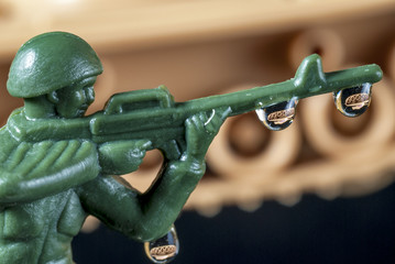 Plastic Army Man with drops and tank reflection