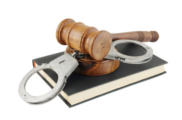 Judge's gavel and handcuffs on black legal book