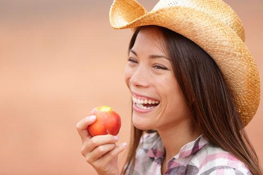 American cowgirl eating peach
