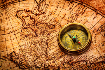 Wall Mural - Vintage compass lies on an ancient world map.