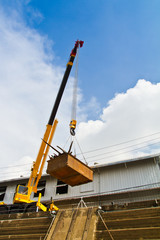 Yellow mobile crane hydraulic boom raises tray over dockyard