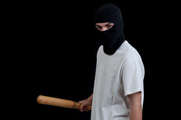 Masked man preparing to attack with bat