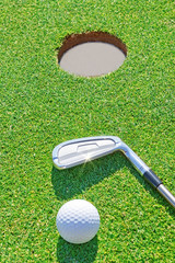 Golf putter ball near the hole in the vertical format. Against t