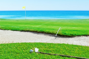 Golf stick and ball on grass against the sea. Rake near the sand