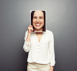 woman covering image with big happy face