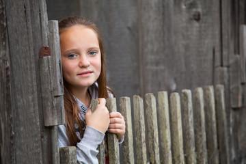 Portrait of teen-girl standing near vintage rural fence.