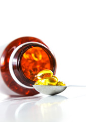 In de dag Thee Capsules of fish oil on spoon with bottle background