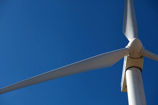 Wind mill, a turbine close against blue sky