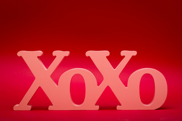 a wood carved X and O's symbol stands up on a red background