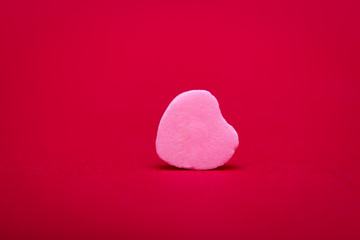 a pink heart shaped candy lies on its side