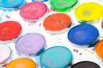 Colorful used watercolor paints in white plastic box