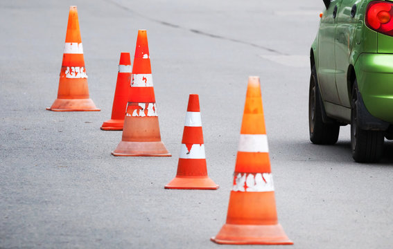 Striped orange cones and car on the asphalt road