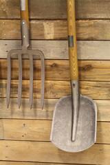 Garden utensils hanging on wooden wall
