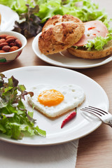 Fried egg on heart-shaped toast with salad for Valentine's Day