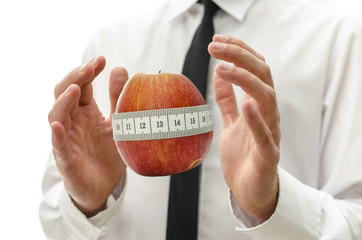 Male hand around apple wrapped with measuring tape