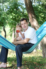 father with his small daughter in a hammock