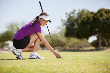 Beautiful woman placing a golf ball on a tee before swinging