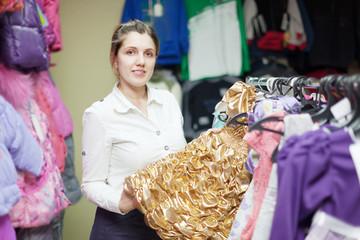 Female buyer chooses gilded dress