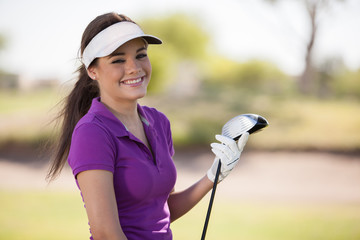 Gorgeous young woman holding a golf club and smiling
