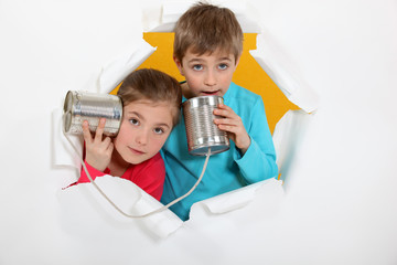 a19a7175e2 Kids having a phone call with tin cans on yellow background - Buy ...