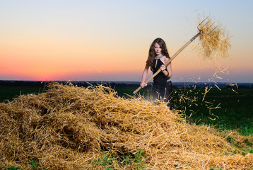 The girl in an evening dress with a pitchfork near a haystack