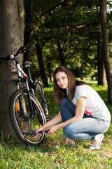 Девушка надувает велосипедное колесо в летнем парке