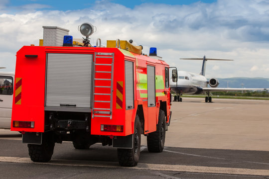 Red airport fire truck driving on tarmac by the airplane