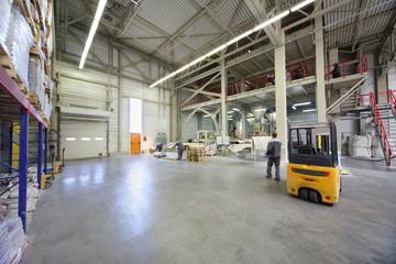 Men in gray uniform work in large warehouse