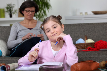 Little girl doing her homework whilst her mom is sewing