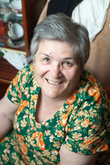 portrait of a smiling senior female in chair
