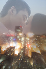 Double exposure of couple kissing over night cityscape