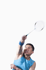 Man playing badminton, white background