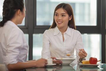 Businesswomen eating breakfast