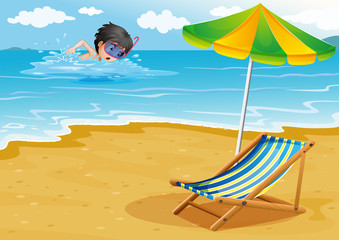 A boy swimming at the beach with an umbrella and a foldable bed