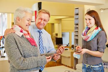 Senior couple buying new glasses at optician