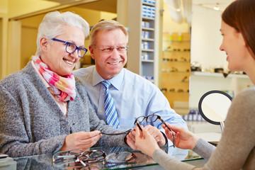 Optician consulting senior couple