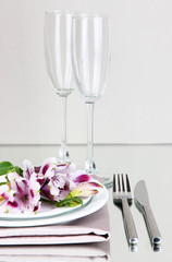 Festive table setting with flowers on grey background
