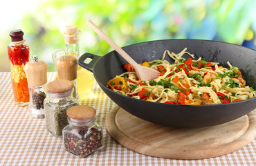 Noodles with vegetables on wok on nature background