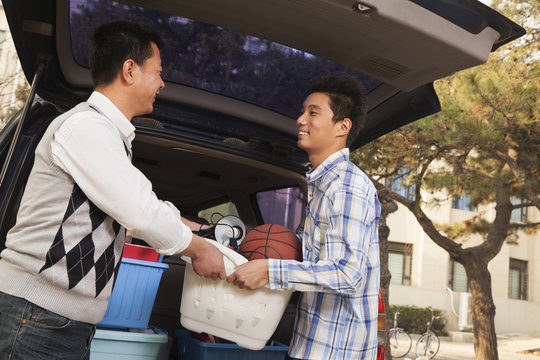 Father and son unpacking car for college