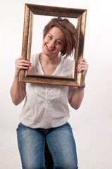 Funny beautiful woman holding around her face a frame