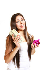 Happy young woman posing with a piggy bank and dollars on a whit