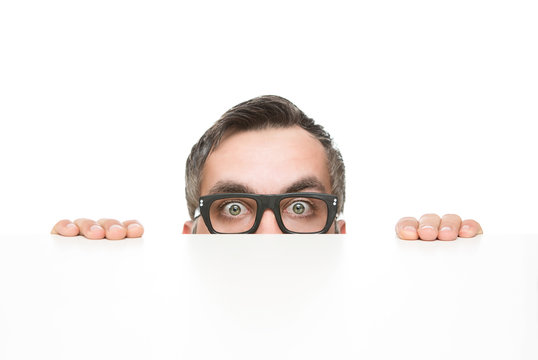 Funny nerd peeking from behind the desk isolated on white