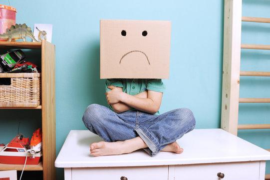 Trotziges Kind mit Karton auf dem Kopf